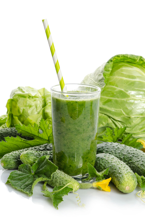 glass with green smoothie  and  vegetables, leaves, flowers  isolated on white background