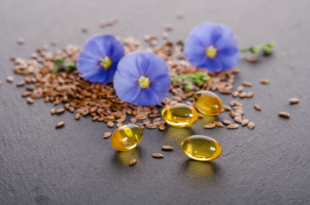 Flax seeds , beauty flower and oil in caps on a grey background. Phytotherapy.