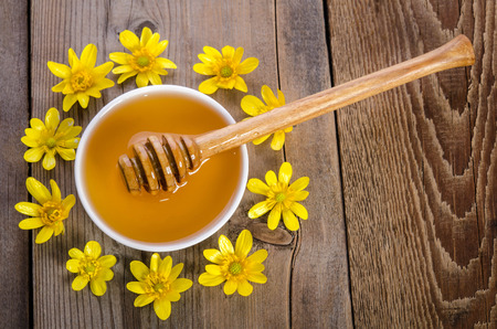 bee on flower: honey in the glass bowl, dipper and yellow flowers around it on wooden background