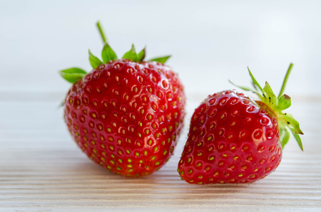 two strawberries on a wooden table Stock Photo