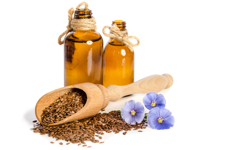 Flax seeds in the wooden scoop, bottles with oil and  beauty flowers isolated on white background.