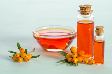 Sea buckthorn and two bottles, bowl  with sea buckthorn oil on blue table