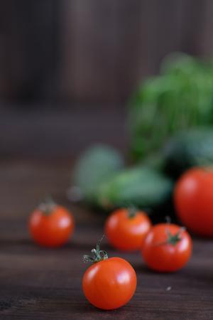 Vegetable.Fresh vegetables: tomatos, cucumbers and green seasonings on  old rustic oak table. Stock Photo