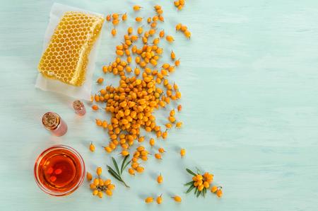 Sea buckthorn, Sea buckthorn oil in glass bottles , honey on blue table. top view