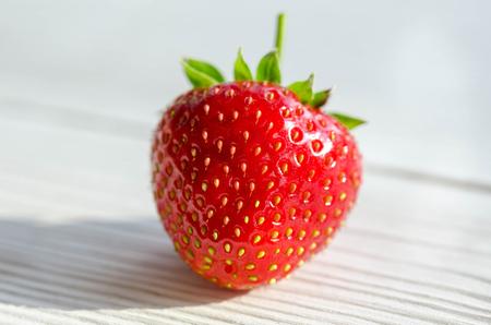 one strawberry on a wooden table Фото со стока