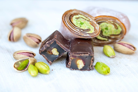 Eastern Turkish sweets with pistachios on a white wooden background. Chocolate candy with pistachios, baklava and pistachio nuts around.