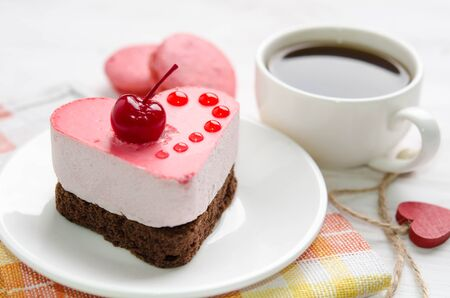 souffle cake in the form of heart  with cup of coffe and macaroons on a wooden table Reklamní fotografie