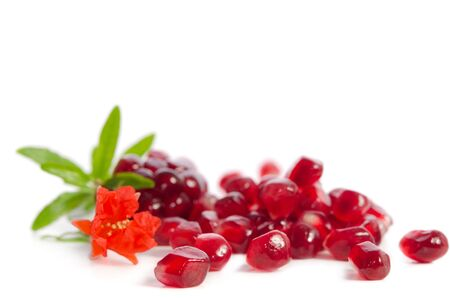 Parts of a pomegranate with pomegranate seeds and leaves, flowers isolated on white
