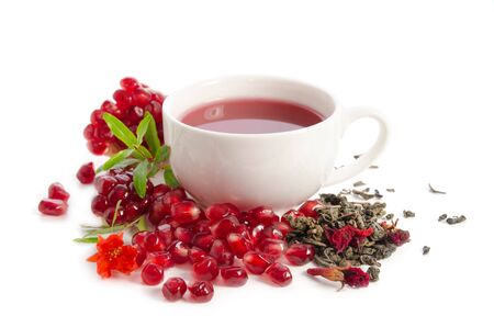 Parts of a pomegranate with pomegranate seeds and leaves, flowers, dry tea of carcade and full cup of tea isolated on white