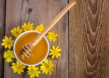 honey in the glass bowl and yellow flowers around it on wooden background