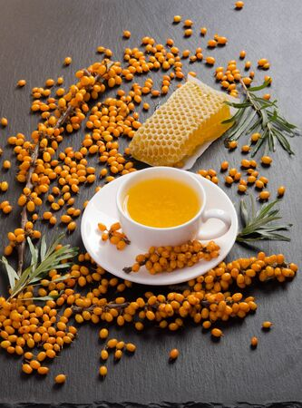 Sea buckthorn, honeycomb with honey and cup of  tea on black stone table.