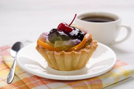 basket cake decorated with different fruit and cup of coffee on white table
