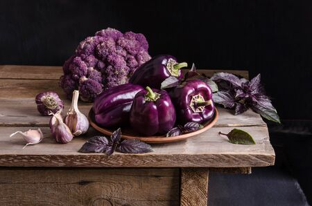 Fresh vegetable. Dark purple peppers, cauliflower with leaves of basil and garlic on old rustic wooden table on black