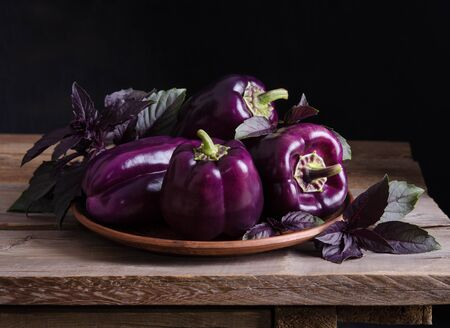 Fresh vegetable. Dark purple peppers in the plate with leaves of basil  on old rustic wooden table on black