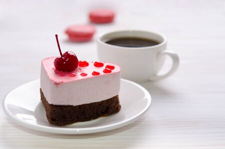Souffle cake in the form of heart  with cup of coffee and macaroons on a wooden table Reklamní fotografie