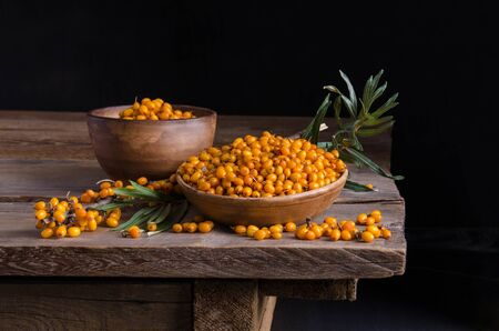 Sea buckthorn in the plate and around Sea buckthorn berries on wooden table