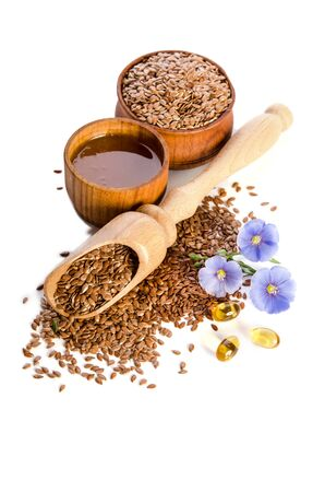 Flax seeds in the wooden scoop, bowl with oil and oil in caps and  beauty flowers isolated on white background. Phytotherapy.  Reklamní fotografie