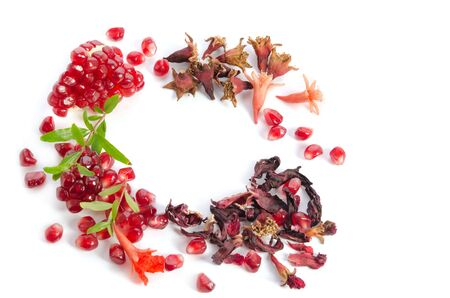 Parts of a pomegranate with pomegranate seeds and leaves, flowers, dry tea of carcade  isolated on white background  Reklamní fotografie
