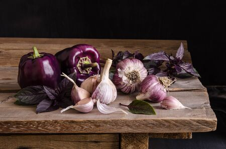 Dark purple peppers with leaves of basil and garlic on old rustic wooden table on black background. Reklamní fotografie