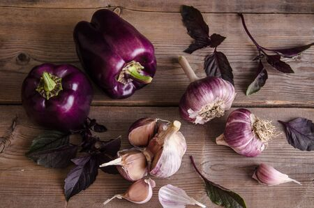 Dark purple peppers with leaves of basil and garlic on old rustic wooden table on black background. Top view