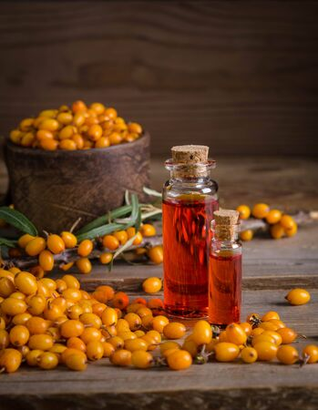Sea buckthorn with bottle with sea buckthorn oil  on wooden table and wooden background