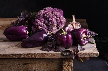 Fresh vegetable. Dark purple peppers, cauliflower with leaves of basil and garlic on old rustic wooden table on black background