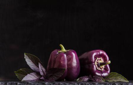 Fresh vegetable. Dark purple peppers with leaves of basil on black stone, black background