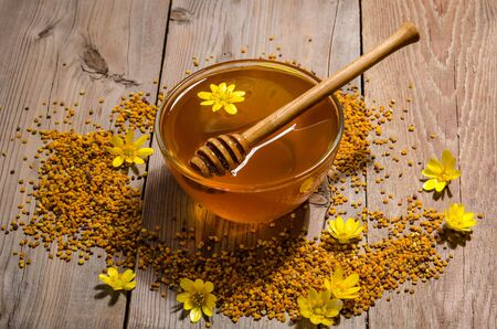 Honey in the glass bowl , pollen and yellow flowers around it on wooden