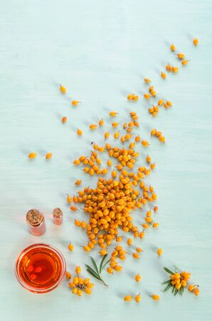 Sea buckthorn with two bottles  and bowl with sea buckthorn oil  on blue table