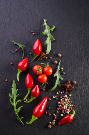 Different spices with tomato and  peppers on a black background