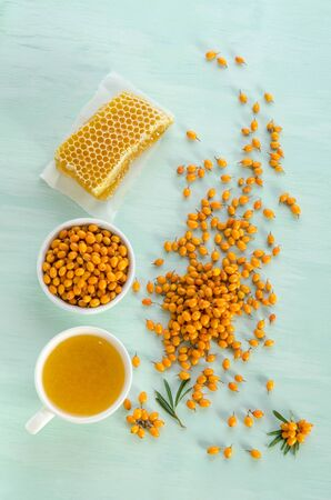 Sea buckthorn in porcelain bowl, honey and cup of  tea with Sea buckthorn on blue table. top view Reklamní fotografie