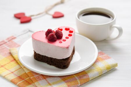 souffle cake in the form of heart  with cup of coffee on a wooden table