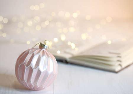 Christmas pink ball, book and garland. Bokeh. Christmas decorations Stockfoto
