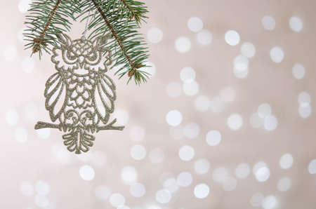 A white toy owl hangs on a Christmas tree branch. Bokeh. Christmas decoration