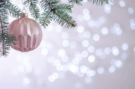 A pink ball hangs on a Christmas tree branch. Bokeh. Christmas decoration