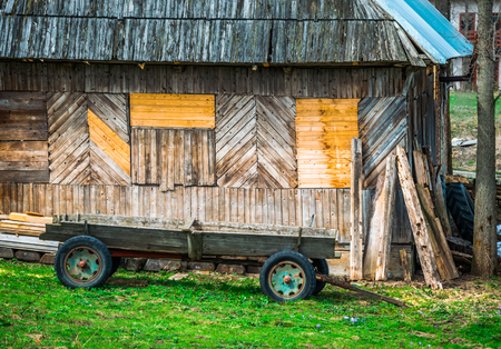 horse and carriage: Vintage wooden cart, horse carriage in the yard near the old wooden house Stock Photo