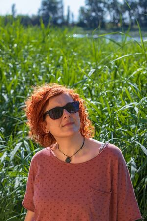 woman redhead watching the sky in the middle of a green field