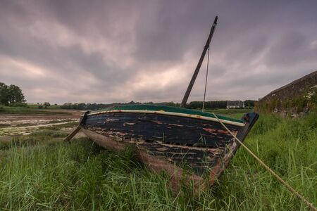 abandoned boat in the brush with a cloudy sky Stock Photo