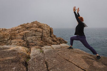 Woman practicing yoga on the coast of Armor pink granite