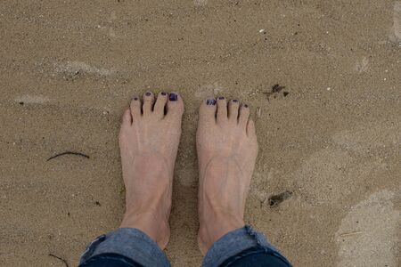 feet of a woman in the sand with painted nails Foto de archivo