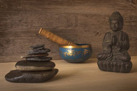 buddha figure, tibetan bowl and stacked stones