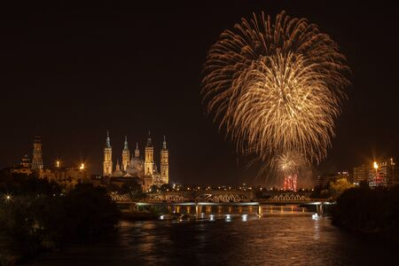 Fireworks in cathedral of our lady of the pilar 13 october 2019 reflected in the ebro river