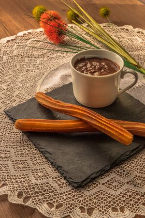 Typical Spanish breakfast, chocolate with churros on handmade tablecloth