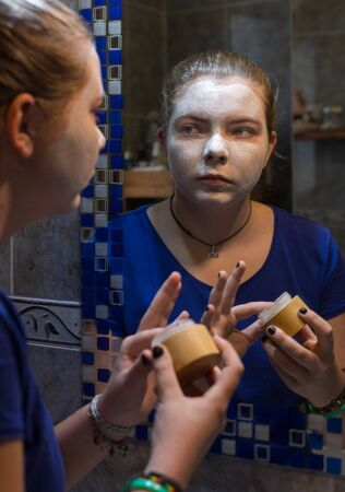 young girl putting cream on her face in front of the mirror Фото со стока