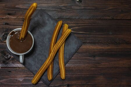 Typical Spanish breakfast, chocolate with churros in a wooden table Stock Photo