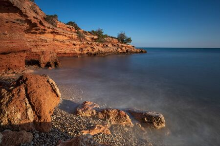 SUNSET ON A ROCKY BEACH in spain long exposure blue and orange tones