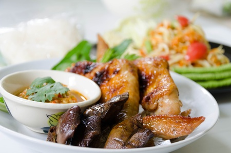 Roasting chicken and grilled liver with sauce and spicy papaya salad somtum