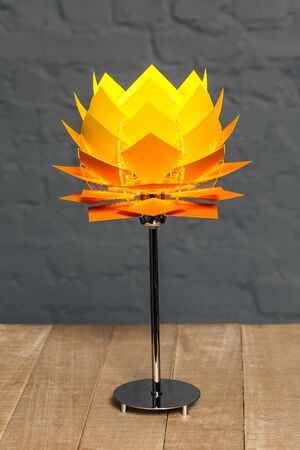 Front view of orange conceptual table lamp on wooden stand on gray brick wall background