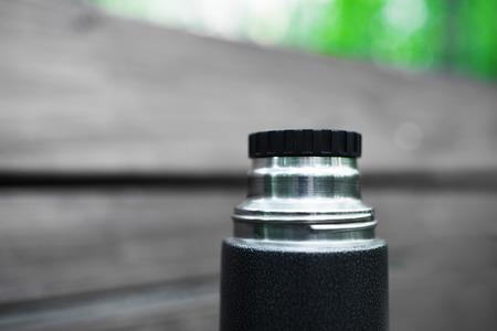 thermos: Horizontal black and white thermos with green bokeh background Stock Photo
