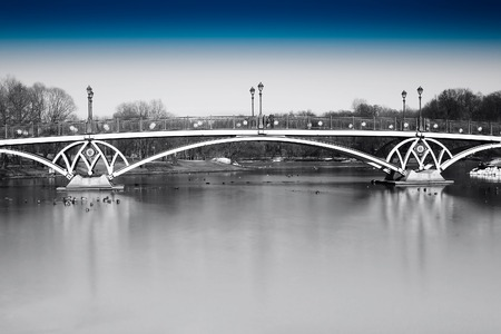 Black and white dramatic arc bridge in Moscow park with blue sky background